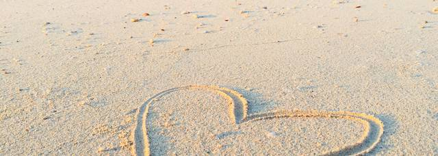 Coeur dessiné sur le sable d'une plage en bord de mer
